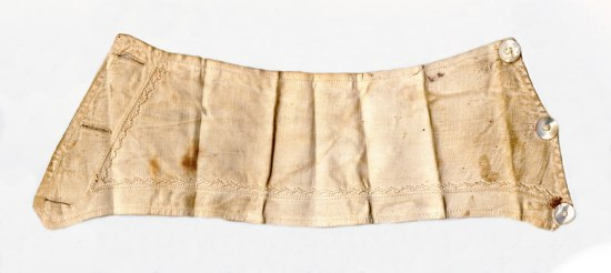 A cuff from a white shirt, with small designs sewn along its border.