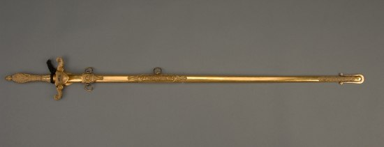 Ornate gold sword in its sheath. A piece of black crepe is tied around the hilt.
