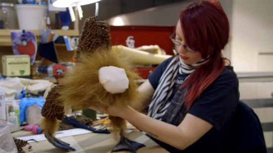 A woman with red hair and glasses holds a model in her hands. It has a poofy mane, webbed feet, and a thickly fuzzy tubular body. Its face hasn't been attached yet and is just a fabric nub. The table on which she holds the model is covered with scissors, supplies, and other craft items.