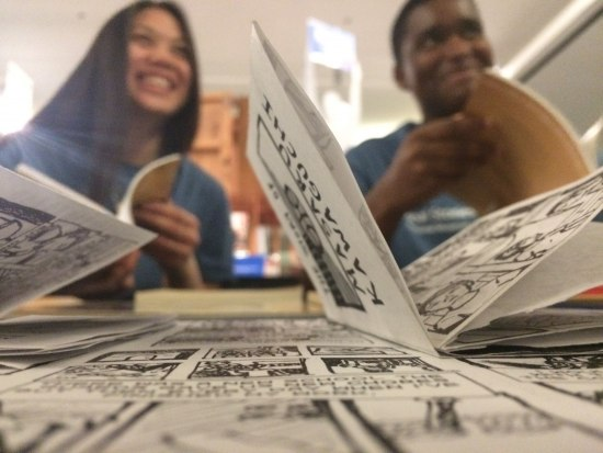 With comic books open in front of them, two teens smile.