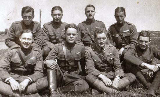 Eight uniformed soldiers sitting on grassy field