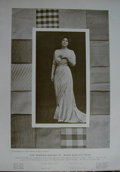 a black and white photograph of a woman in a cream colored dress with a draped skirt, laid on top of pieces of fabric of varied textures and colors