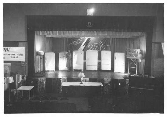 """Black and white photo of a woman on a stage. On stage are six fridges, two lamps, and a big banner that says """"REA."""" On a table on the floor in front of the stage, a lamp. There are decorative tassels."""