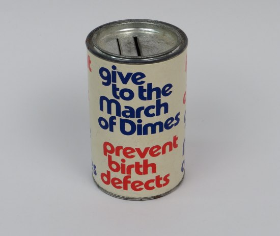 """A tin with a slot in the top for coins. The side of the can reads """"Give to the March of Dimes. Prevent Birth Defects."""""""