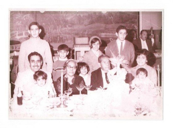 Martinez and his family pose together for a photo while seated at an elaborately decorated table.