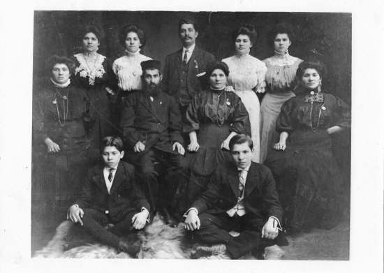 Historic portrait in black and white of family group, including two tween or teen sons. A bearded man in center wears a hat. Six women and one other man appear in the image.