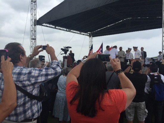 Crowd of people, some holding up phones to take photos, observe activity on a covered stage with a cloudy sky in the background. On stage, people in uniform are presented with medals.