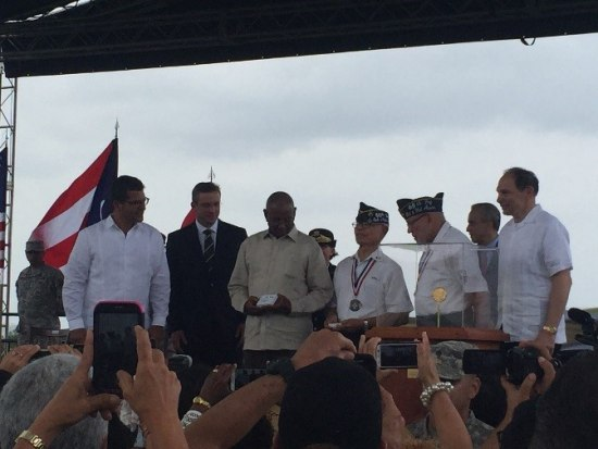 Photo on the stage. Group of men pose, some smiling and holding medals. In background, a flag and cloudy sky.