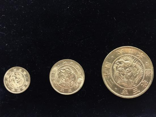 Three gold coins, arranged by size, from small to large