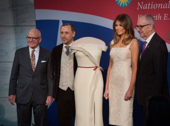 Smithsonian leaders, fashion designer, and Melania Trump pose with her inaugural gown in front of a red, white, and blue backdrop.