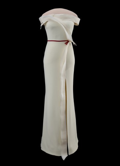 Photo of white gown in front of black background. It's off-the-shoulder with a cross-body sash in front along with red/maroon tie at waist. Narrow silhouette and slit cascading on one side. Glossy and matte fabric in subtle layers.