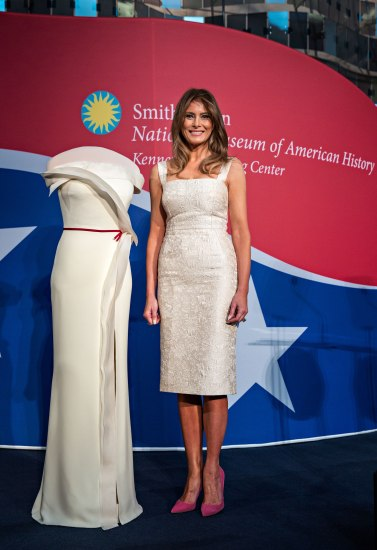 Posted photo on stage. On left, white gown on a form. On right, First Lady Melania Trump smiling beside her gown.