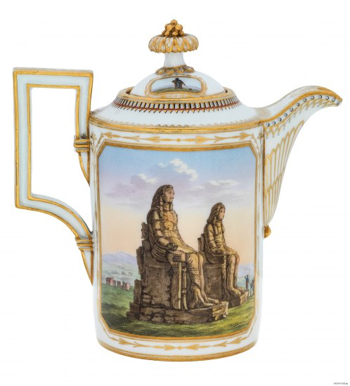 A milk kettle with gold decoration. There is a vignette painted on it of two large stone sitting figures on a plain in front of some ruins farther back and a group of people pointing