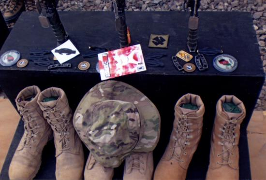Three pairs of military boots, three rifles, three dog tags, and badges/patches worn on uniforms