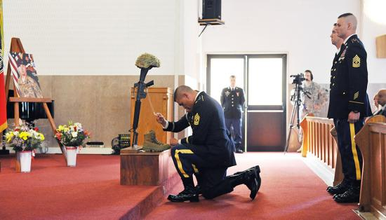 A member of the military kneels in front of a battlefield cross at a memorial ceremony