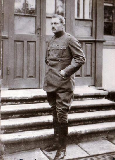 Portrait photograph of man standing on steps in German uniform