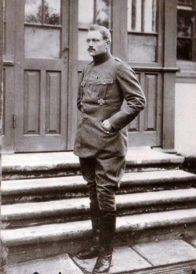 Portrait photograph of man standing on steps in German uniform