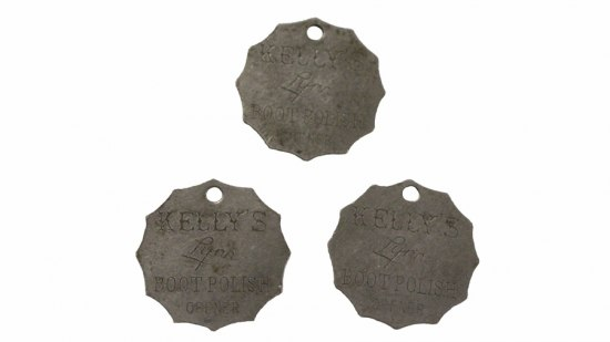 "Photograph of three metal tokens using in Cotton's shop, 1950s–1990s. The token have diveted edges and are stamped with the text, ""Kelly's Lynn Boot Polish Opener."""