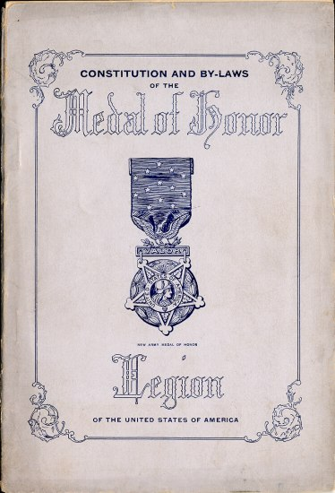The cover of a booklet or publication. There is a drawing of a medal in the middle and text above and below. There is a border with flourishes in the corners.