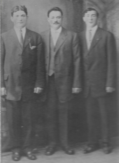 Black and white photo of three men in suits, standing