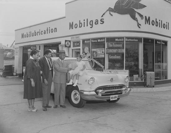 Photograph of an African American businessman presenting an Oldsmobile to raffle winners in 1955.