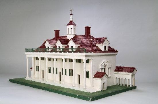 Model of a home. It has eight columns in the front, with three doors and many windows with green shutters. It is mostly white with a red brick roof.