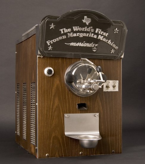 "Brown machine with text ""The World's First Frozen Margarita Machine / Mariano's"" with stars and image of state of Texas. Pour spout and drip cup in front."