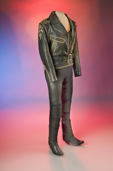 A black leather jacket with gold detailing, slim pants and boots positioned upright on a headless mannequin in from of a colorful backdrop of reds and blues