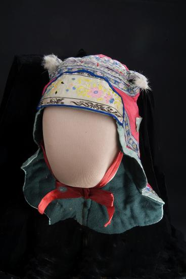 Photo of bonnet with colorful floral designs. It covers the child's neck and has two ears on top, like a dog or other mammal. Tied with a red ribbon under chin.