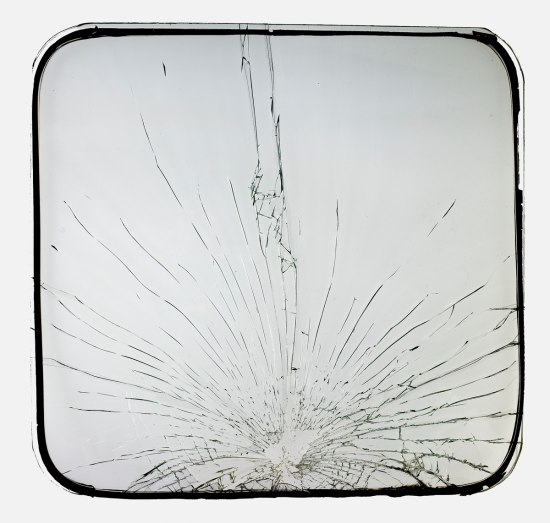 Photograph of broken bus window. Cracks from an impact radiate from the window's bottom third.