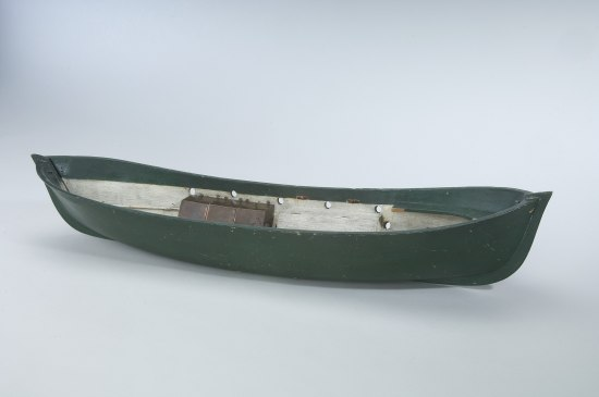 Model of a small boat. Shaped like a canoe. White on inside, green on outside.