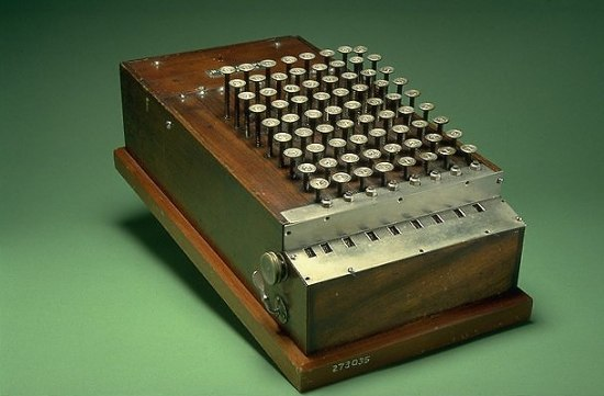 A dark wooden box sits against a green background. It looks like a typewriter, with metal keys protruding from the top and metal covering the front.
