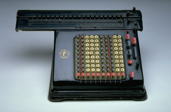 A black metal machine that resembles a typewriter. Instead of letters the keys have numbers and are different colors in rows.