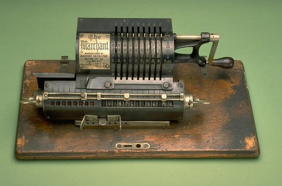 a machine with a wooden base that looks like a typewriter or old-fashion crank handled music player. There are numbers on a roll on the bottom front of the device.