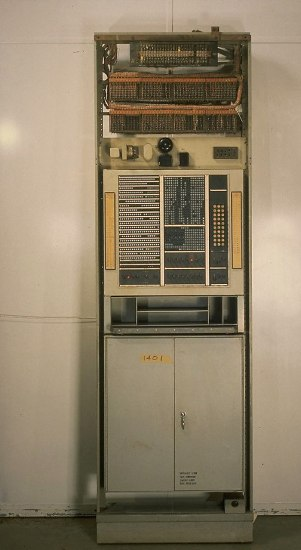 A standing structure with a metal cabinet built into the bottom and a complex array of buttons and switches going up its front. There appear to be coils like a radiator at the very top. Looks like a rudimentary standing computer server.