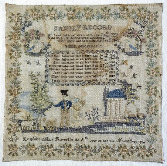 Photo of sampler with text, floral decor, figure, building, two birds, and small mammals (sheep?)