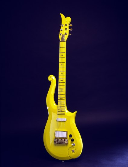 A bright yellow guitar against a dark blue backdrop. It is rounded and has a tendril-like portion stretching up the length of the instrument.