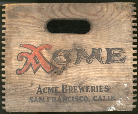 "Wooden panel of a crate with a hole where you put your hand to lift it. ""ACME"" is painted in red and black."