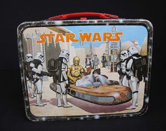 Lunch box featuring a scene from Star Wars. Three characters are in a vehicle that has been stopped by storm troopers.