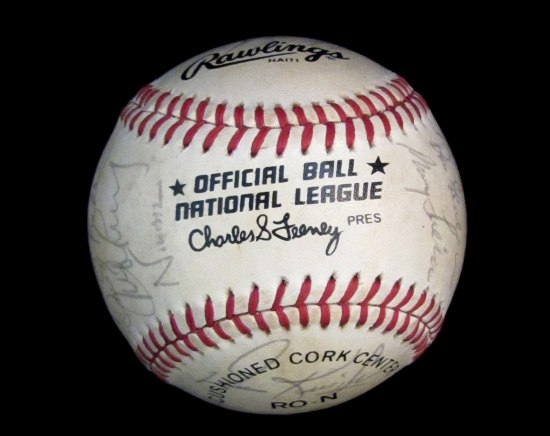 "Photo of baseball with red thread. Text on ball: ""Official Ball National League"""