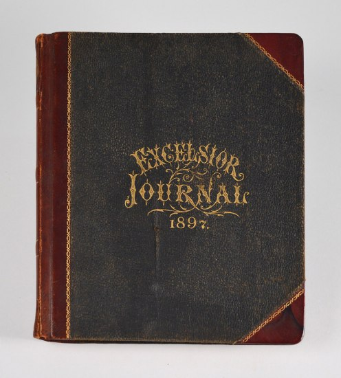 "Photograph of the cover of the museum 1897 mining journal. The cover's text reads ""Excelsior Journal 1897"" in dramatic gold font."