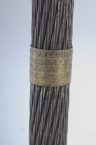 "Metal cords with plaque that reads  ""ATLANTIC TELEGRAPH CABLE/GUARANTEED BY/TIFFANY & CO./ BROADWAY • NEW YORK • 1858."""