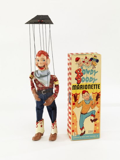 "Photo of a marionette with red hair, freckles, blue jeans, plaid shirt, black strings, and boots. Also box labeled ""Howdy Doody."""