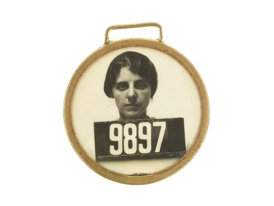 Circular pin with a gold or grass colored frame. Inside, a black and white portrait of a women, like an ID badge. Her hair is tucked back and face is serious. Her ID number is 9897.