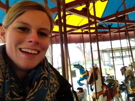 Selfie of young woman smiling with carousel horses in the background