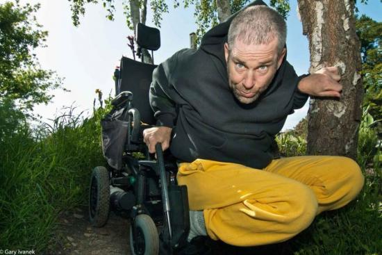 Daytime outdoor photo of man crouching out of wheelchair. He wears yellow pants.