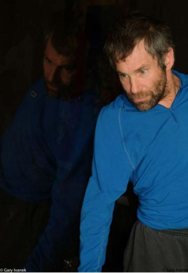 Color photo of man with brown hair and beard, with intense expression in his wide eyes. Blue shirt, gray pants. Slightly reflection in background.