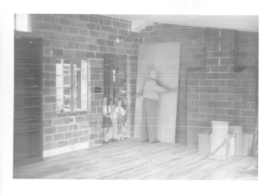 A black and white photograph of a man facing a wall and holding a large sheet of wood in a room with wood floors and brick walls. Two children stand in the doorway next to him.