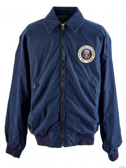 Man's jacket on a form. It is dark navy and collared with a zipper down the front. On left breast, Presidential seal.