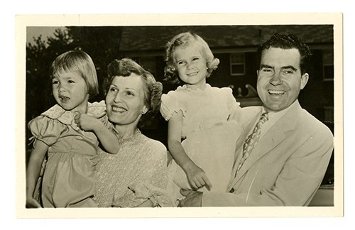 A photograph of Richard Nixon and his family. He and his wife each hold a child, who are quite young in the picture. They are smiling.